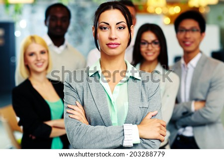 Beautiful businesswoman with arms folded standing in front her colleagues