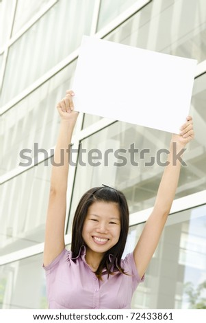 Beautiful businesswoman with blank paper for advertisement - stock photo