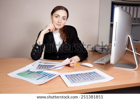 Beautiful businesswoman with financial report at office - stock photo