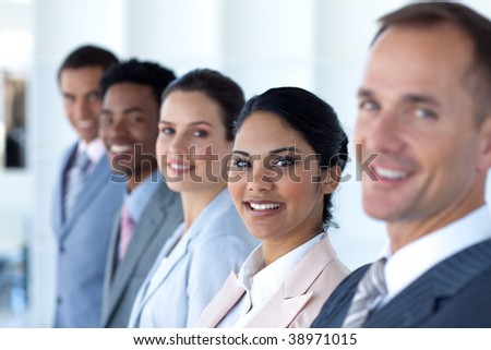 Beautiful businesswoman with her team in a line smiling at the camera - stock photo