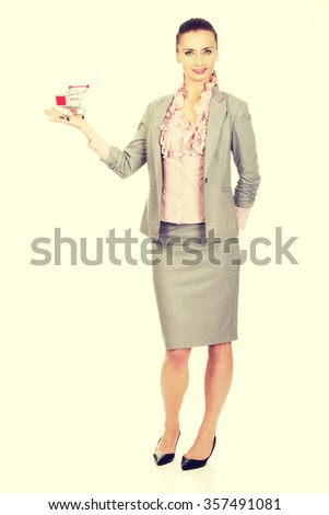 Beautiful businesswoman with shopping cart. - stock photo