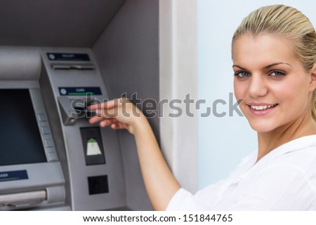 Beautiful businesswoman withdrawing money from credit card at ATM