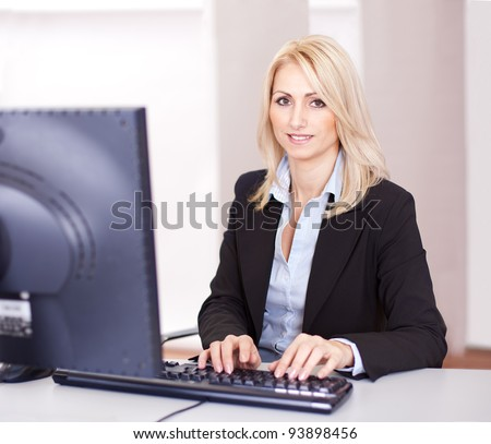 Beautiful businesswoman working on computer in the office - stock photo