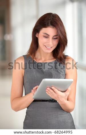 Beautiful businesswoman working on electronic tab - stock photo