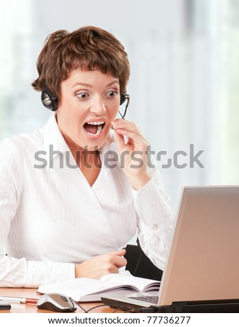 Beautiful  businesswoman working with laptop and headset at her office - stock photo