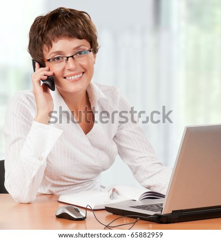 Beautiful  businesswoman working with laptop holding a mobile at her office - stock photo