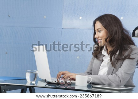 Beautiful businesswoman working with laptop in office - stock photo