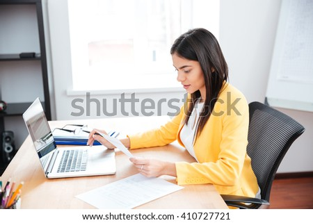 Beautiful businesswoman working with papers and laptop computer in office
