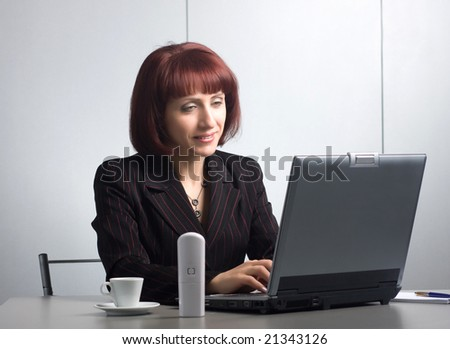 Beautiful businesswomen behind a table and a laptop - stock photo