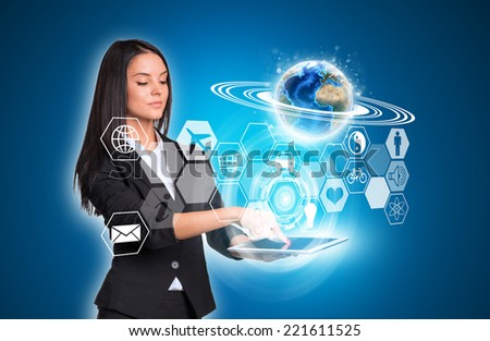 Beautiful businesswomen in suit using digital tablet. Earth and transparent hexagons with icons. Element of this image furnished by NASA
