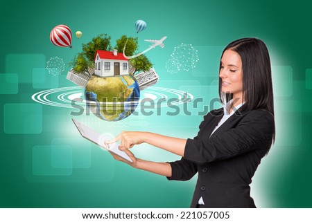 Beautiful businesswomen in suit using digital tablet. Earth with house, buildings, air balloons, trees and airplane. Element of this image furnished by NASA - stock photo