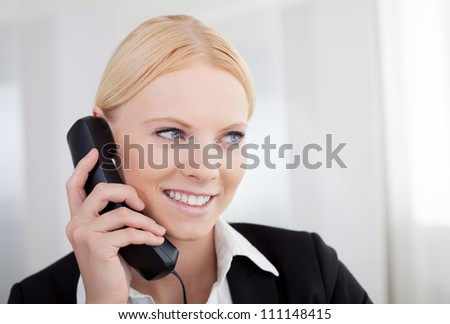Beautiful businesswomen talking on the phone in the office - stock photo