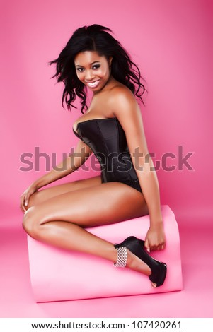 Beautiful busty African model with a lovely smile posing on a pink pouffe in a corset to enhance her large protruding breasts
