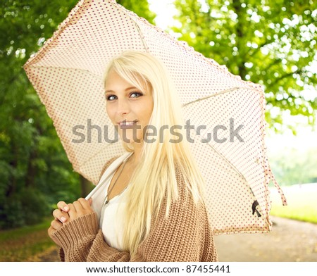 Beautiful busty young blonde girl with umbrella under trees in park. - stock photo