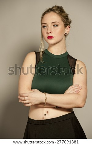 Beautiful busty young female brunette with straightened hair in a studio setting while wearing a green top and a short black mini skirt on a gray background. - stock photo
