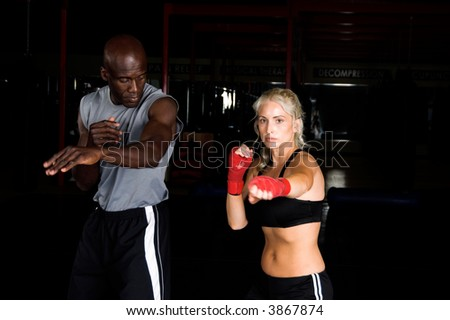 Beautiful but dangerous female fighter working on her right cross with her trainer in an Mixed Martial Arts gym. - stock photo