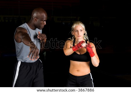 Beautiful but dangerous woman fighter practicing her right cross with her trainer in an Mixed Martial Arts gym. - stock photo
