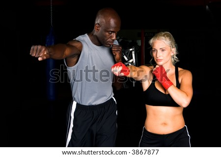 Beautiful but dangerous woman fighter working on her right cross with her trainer in an Mixed Martial Arts gym. - stock photo