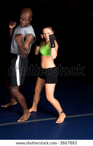 Beautiful but dangerous woman fighter working on her upper cut with her trainer in an Mixed Martial Arts gym. - stock photo