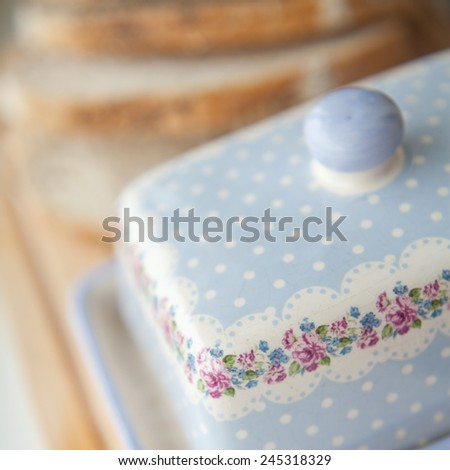 Beautiful butter dish with lovely pink flower pattern and white dots on a blue background. Breakfast preparation. White bread on a background. MAcro perspective, nobody, home related, food - stock photo