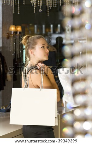 beautiful buyer with fawny bag in the boutique - stock photo