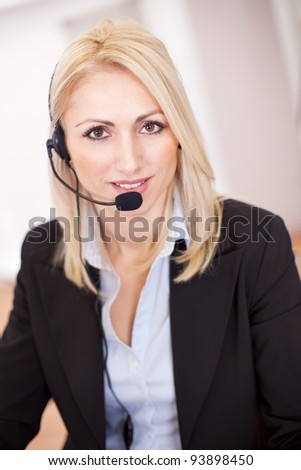 Beautiful call center operator talking over the phone in the office - stock photo