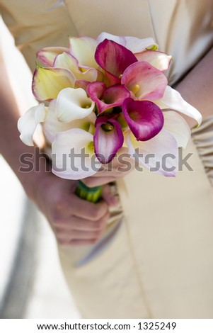 beautiful calla lillies on silk dress with hands wedding bouquet detail - stock photo
