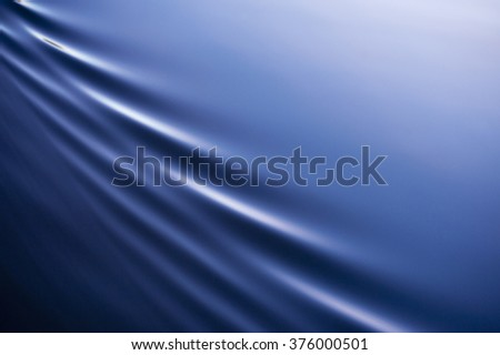 Beautiful, calm blue water is broken by elegant, diagonal ripples with lots of copy space. - stock photo