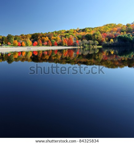 Beautiful calm lake in the fall reflecting trees - stock photo