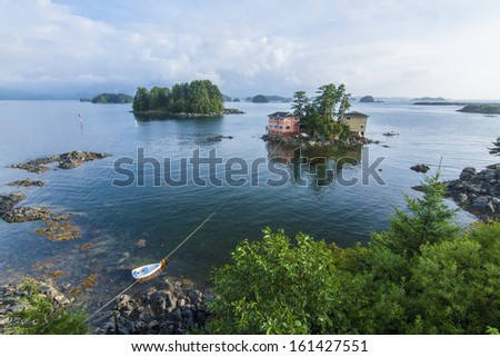 Beautiful calm summer, seascape with boat and houses on tiny forested islands in Sitka Sound on Baranof Island, Alaska - stock photo