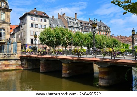 Beautiful canals of Strasbourg, France with flower lined bridge - stock photo