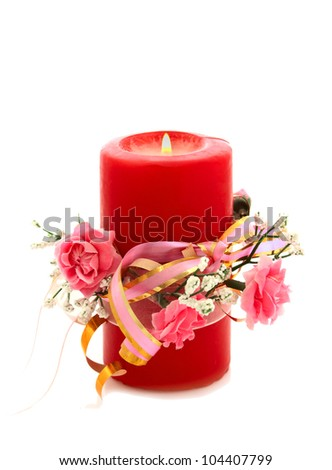 beautiful candle decorated with artificial  flowers over white