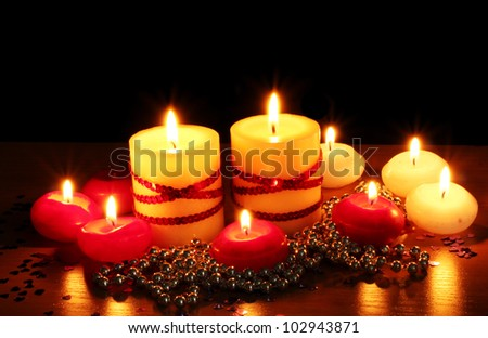 Beautiful candles and decor on wooden table on black background