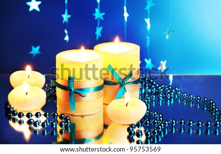 Beautiful candles, gifts and decor on blue background - stock photo