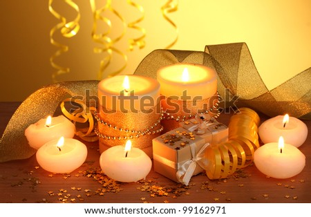 Beautiful candles, gifts and decor on wooden table on yellow background - stock photo
