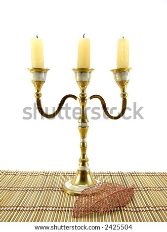 Beautiful candlestick and leaf on a bamboo napkin