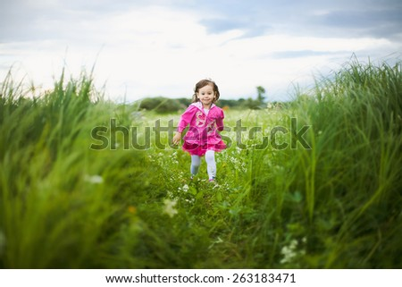 beautiful carefree girl playing outdoors in field with high green grass.freedom concept - stock photo
