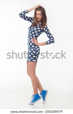Beautiful carefree teenager in lace up shoes with a tender smile walking in a pretty blue and white polka dot sundress. Isolated on white. Concept of youth, attraction and freedom - stock photo