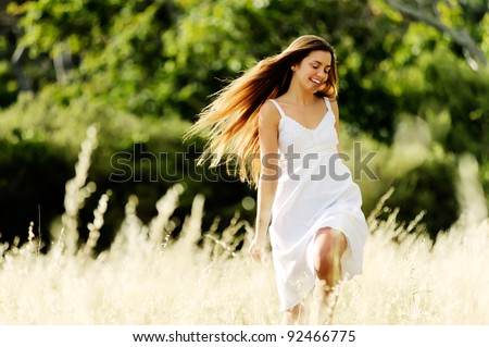beautiful carefree woman skips and plays outside, cheerful and smiling