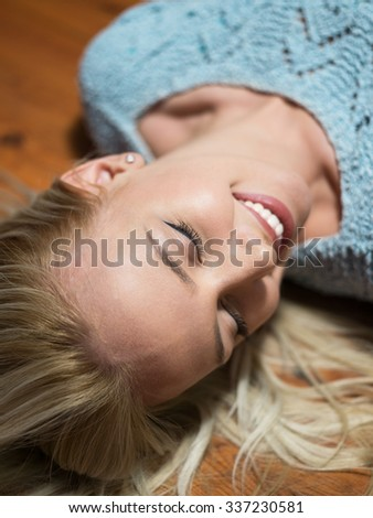 Beautiful carefree young casual woman lying on the wooden floor.