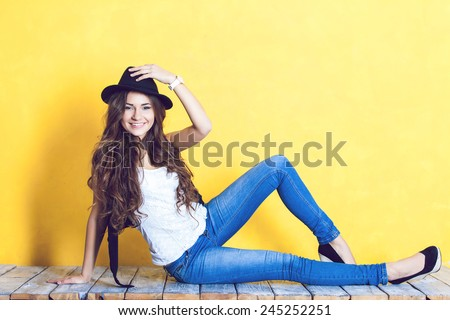Beautiful carefree young casual woman on the wooden floor. - stock photo