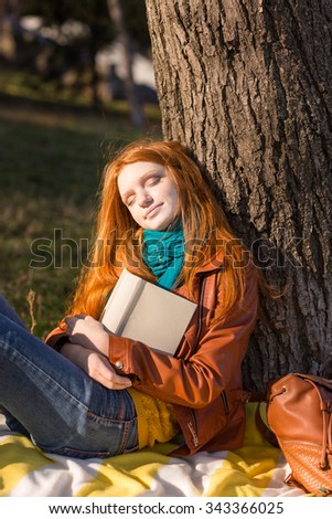 Beautiful carefree young redhead lady in leather jacket and jeans sleeping under the tree in park - stock photo