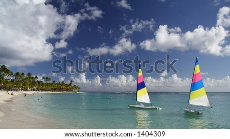 Beautiful caribbean lagoon with two colorful jolly boats - stock photo