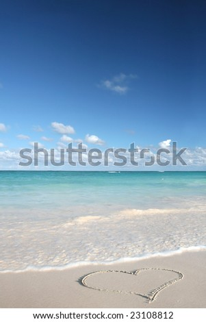Beautiful Caribbean tropical beach with a big heart drawn on white sand and green ocean, suitable background for a variety of traveling and holiday/love designs - stock photo