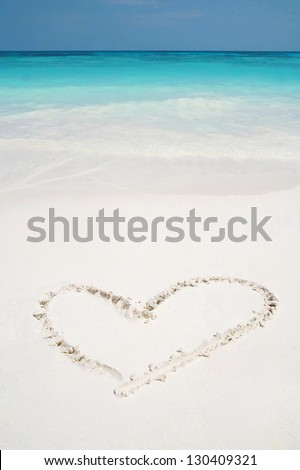 Beautiful Caribbean tropical beach with a heart drawn on white sand and green ocean - stock photo
