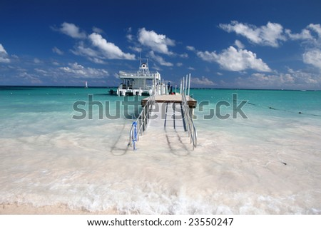 Beautiful Caribbean tropical beach with white sand and a white ferry in green ocean, suitable background for a variety of designs - stock photo