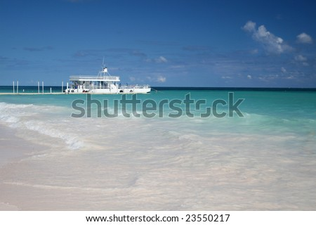 Beautiful Caribbean tropical beach with white sand and ferry boat in green ocean, suitable background for a variety of designs - stock photo