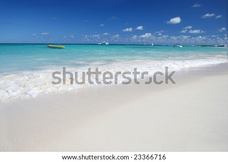 Beautiful Caribbean tropical beach with white sand and green ocean, Dominican Republic, suitable background for a variety of designs. FOCUS on the edge of the rolling wave. - stock photo