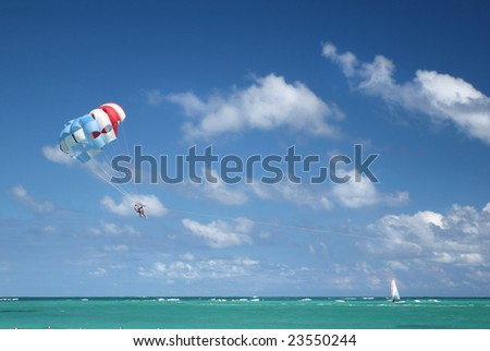 Beautiful Caribbean tropical ocean with two people parasailing, suitable background for a variety of designs - stock photo