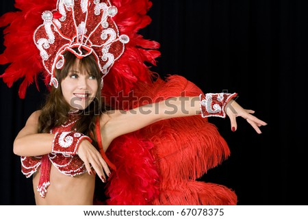 Beautiful carnival dancer in red feather costume - stock photo